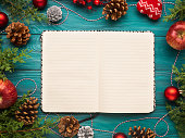 Open notebook on christmas background with pine cones and ornaments. Festive flat lay with white pages
