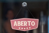 """Old fashioned sign in the window of a shop saying in Portuguese """"Aberto"""", meaning in english """"Open""""."""