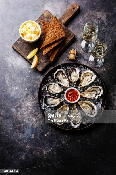 Open Oysters with bread and butter and champagne on dark texture background copy space