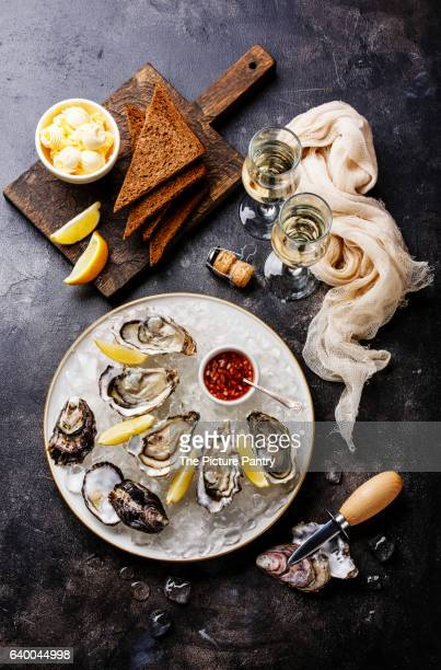 Open Oysters with bread and butter and champagne on dark texture background