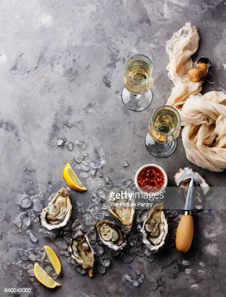 Open Oysters with sauce and champagne on gray concrete texture background copy space