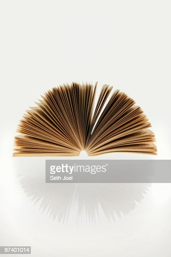 Open paperback book on reflective surface : Stock Photo
