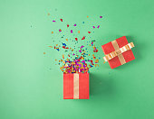Open red gift box with various party confetti on a green background. Flat lay