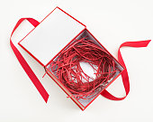 Open red & white gift box with red shredded paper & grosgrain ribbon tie.