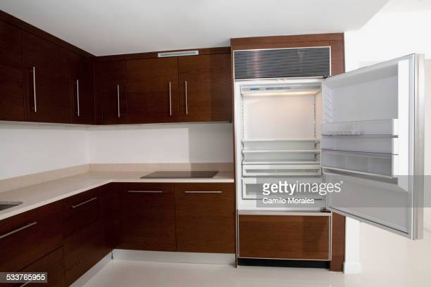 Open refrigerator in empty kitchen