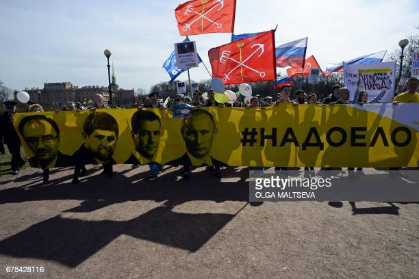 'Open Russia' party supporters hold a banner with portraits of Russian President Vladimir Putin Prime Minister Dmitry Medvedev Chechen leader Ramzan...