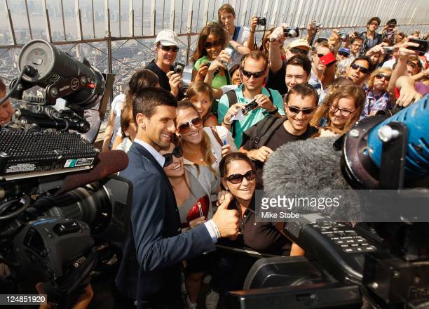 Open Singles Men's Champion Novak Djokovic of Serbia poses with fans atop the Empire State Building on September 13 2011 in New york City New York...