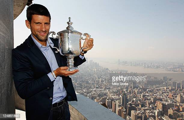 Open Singles Men's Champion Novak Djokovic of Serbia poses with his trophy atop the Empire State Building on September 13 2011 in New York City New...