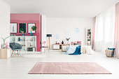 Open space bedroom interior with big rug, cozy bed, pink and white walls, chairs, posters, basket, pink drapes and bookcases