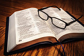 Open Study Bible On Table With Glasses
