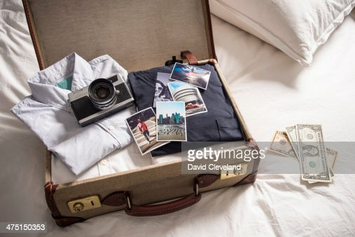 Open suitcase on bed with camera and photographs