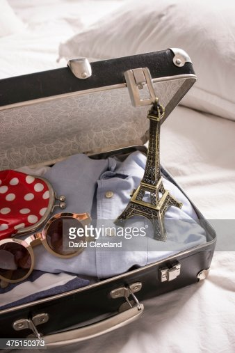 Open suitcase on bed with eiffel tower souvenir and sunglasses