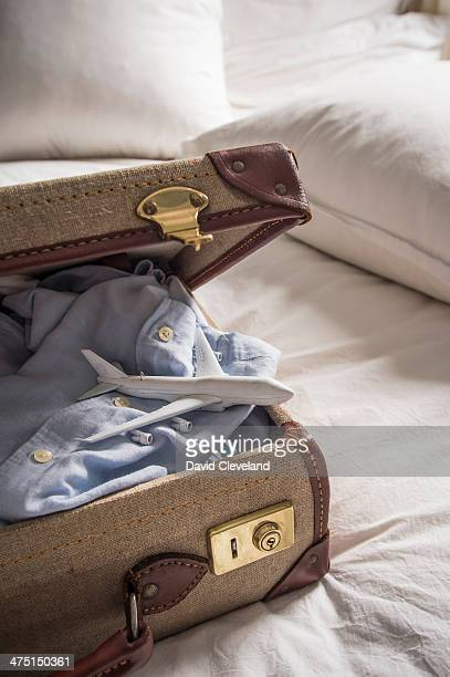 Open suitcase on bed with shirt and toy airplane