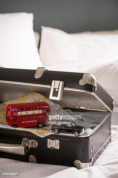 Open suitcase on bed with toy London bus and black cab