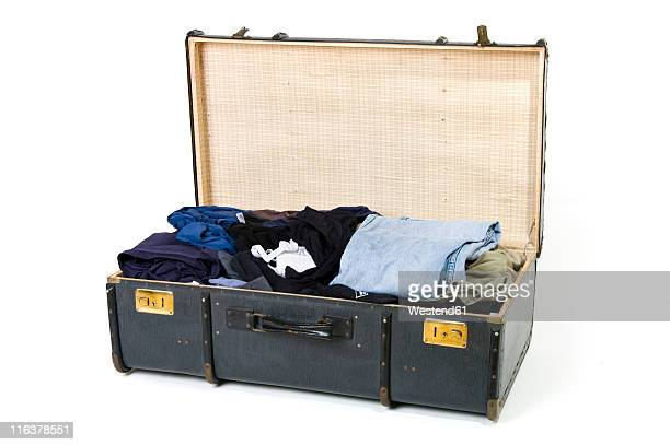 Open suitcase with clothes on white background