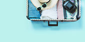 Open suitcase with female clothes for trip on pastel blue background. Top view with copy space. Summer concept travel.