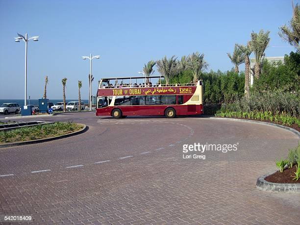 Open top red tour bus in front of Atlantis The Palm hotel in Dubai