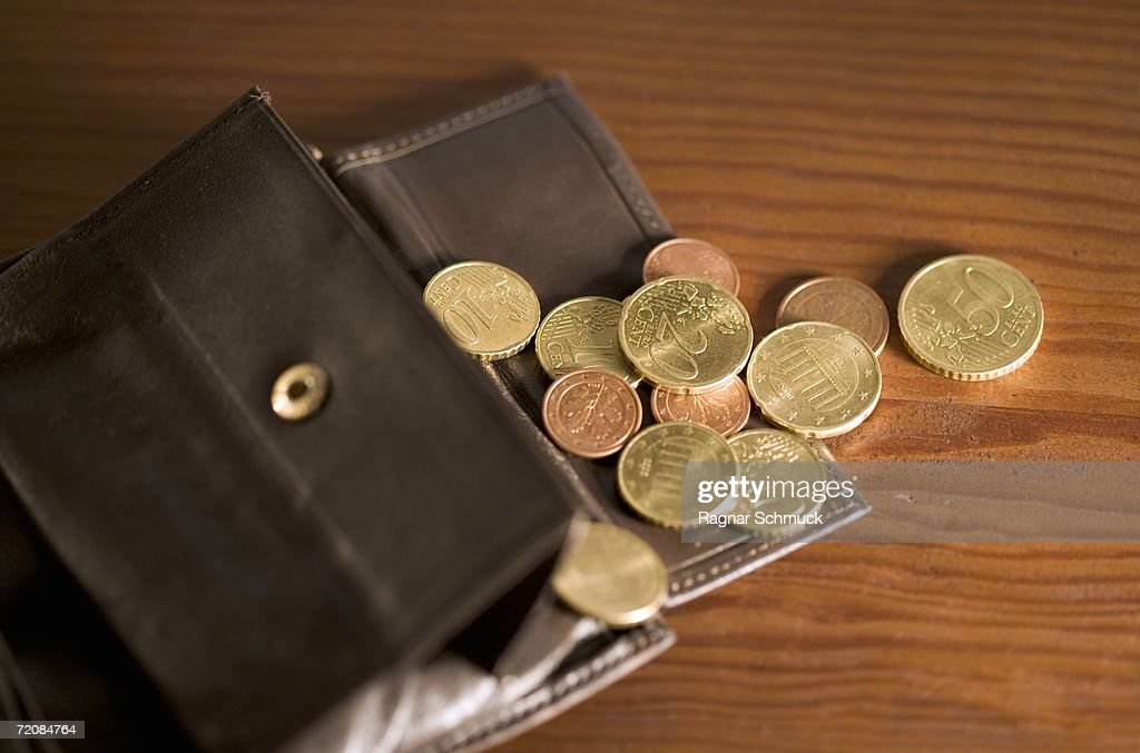 Open wallet with coins spilling onto table