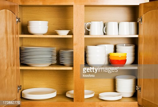 Open wood cupboard shelving plates dishes and jugs