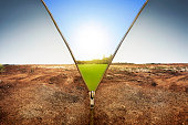 Open zipper showing dry land landscape changing to green land landscape with sunlight background
