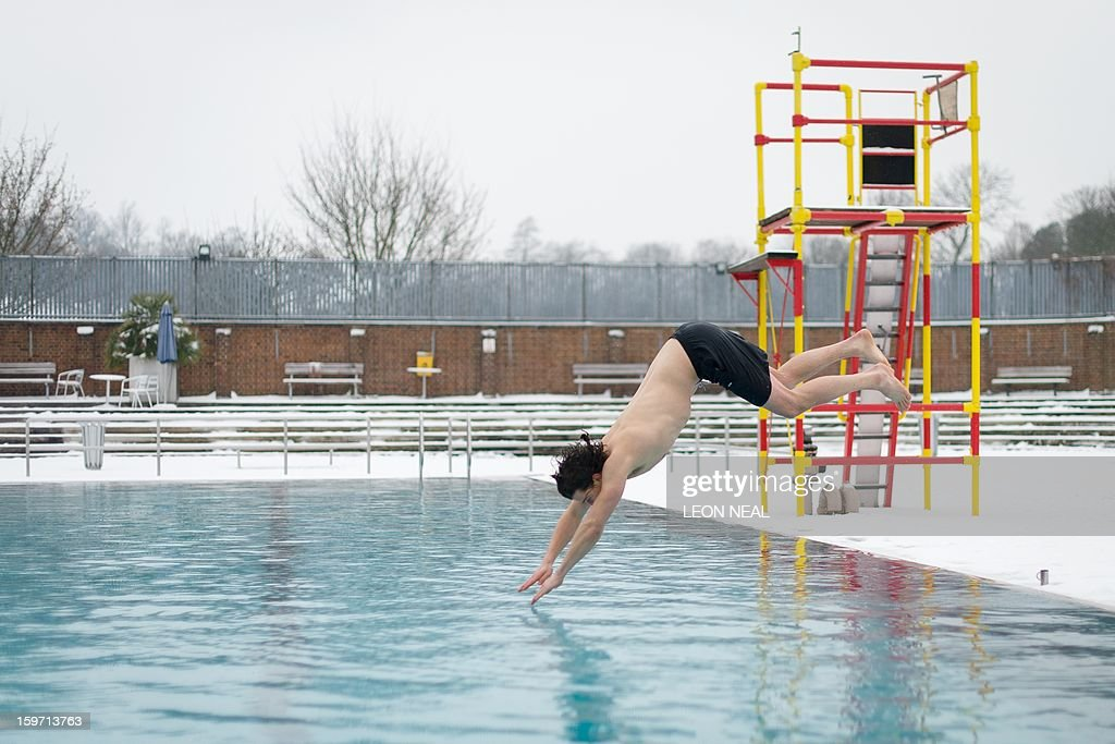 Open-air swimming enthusiast Chai Anich dives into the waters of a lido in north London on January 19, 2013. While some people are savouring the cold conditions, snow that swept across Britain on January 18 continues to cause travel difficulties across the country. AFP PHOTO / LEON NEAL