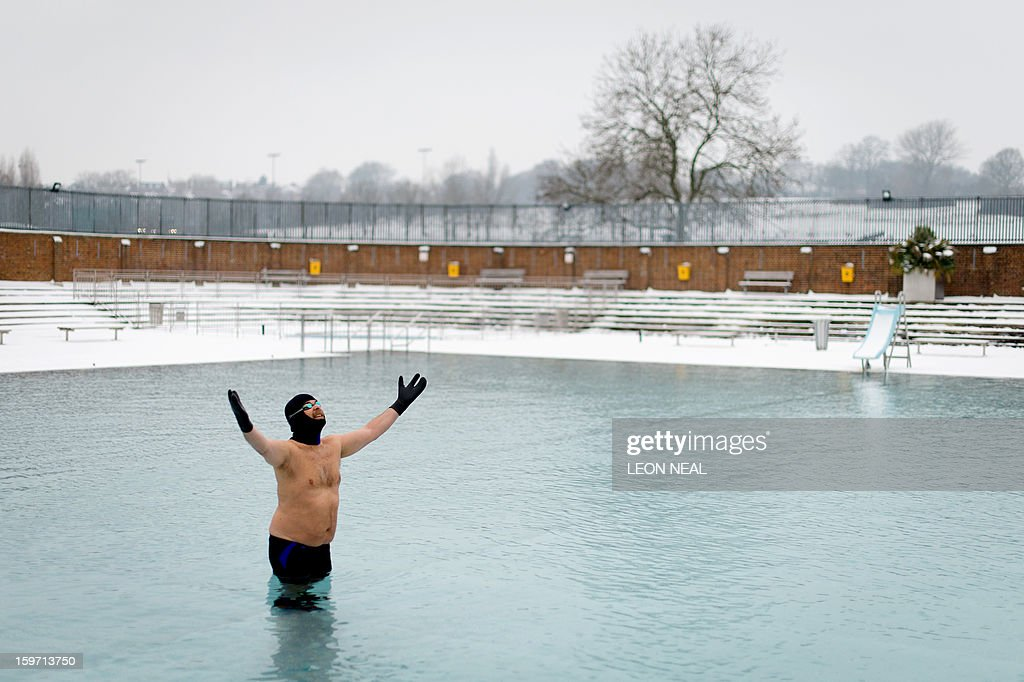 Open-air swimming enthusiast Ovidio Salazar swims lengths in the icy waters at a lido in north London on January 19, 2013. While some people are savouring the cold conditions, snow that swept across Britain on January 18 continues to cause travel difficulties across the country. AFP PHOTO / LEON NEAL