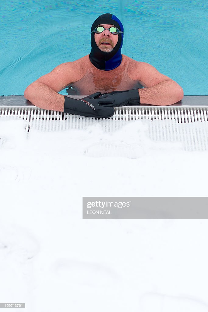 Open-air swimming enthusiast Ovidio Salazar swims lengths in the icy waters at a lido in north London on January 19, 2013. While some people are savouring the cold conditions, snow that swept across Britain on January 18 continues to cause travel difficulties across the country.