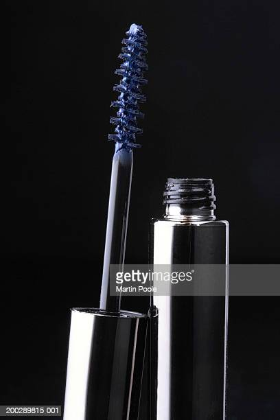 Opened blue mascara wand and pot against black background, close-up