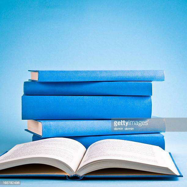 Opened book against stack of books isolated on blue background