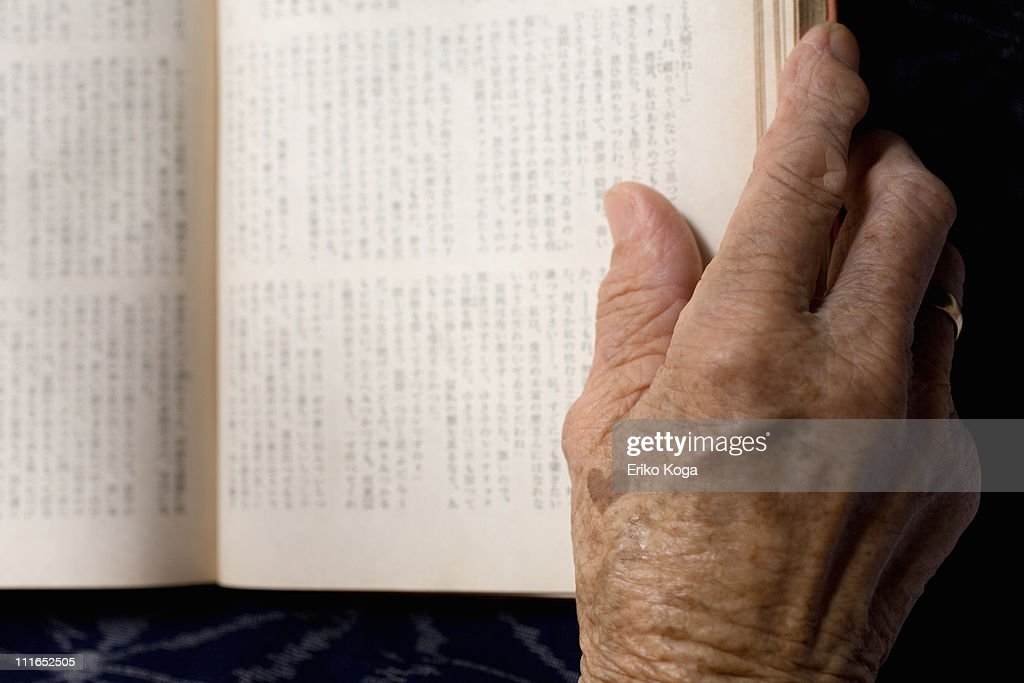 Opened book with hand : Stock Photo