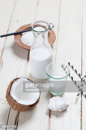 Opened coconut, glass and carafe of homemade coconut milk and coconut flakes