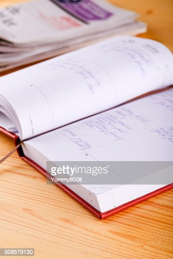 Opened diary with newspapers on light wooden board : Stockfoto