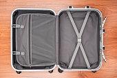 Opened empty travel bag on wooden floor