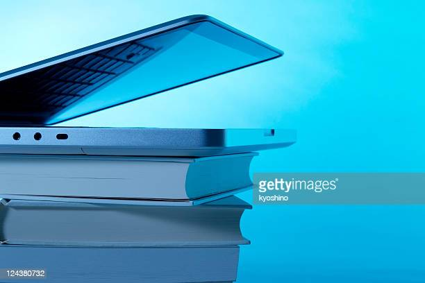 Opened laptop on stacked blank books with copy space