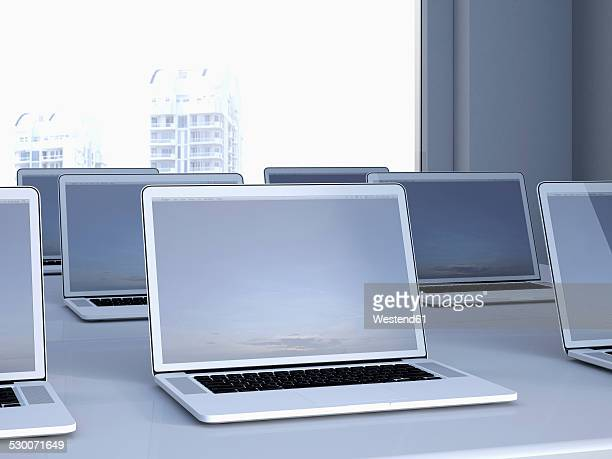 Opened laptops on a table in a n office, 3D Rendering