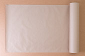 Opened roll of plain brown paper on cardboard for creative artistic designs or craft work, overhead view with copy space