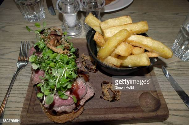 Open-faced sandwich of rare roast beef with watercress served with fried potato chips