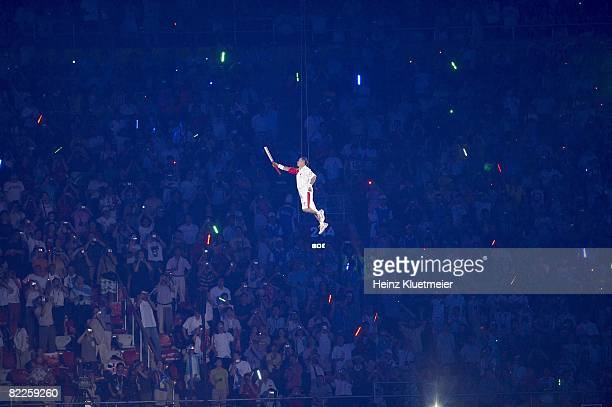 2008 Summer Olympics Former Chinese gymnastics athlete Li Ning carrying torch with flame while being raised with wires to light cauldron at National...