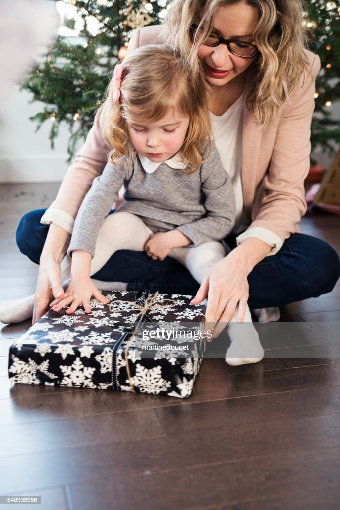Opening gifts on Christmas morning for mother and daughter. : Stock Photo