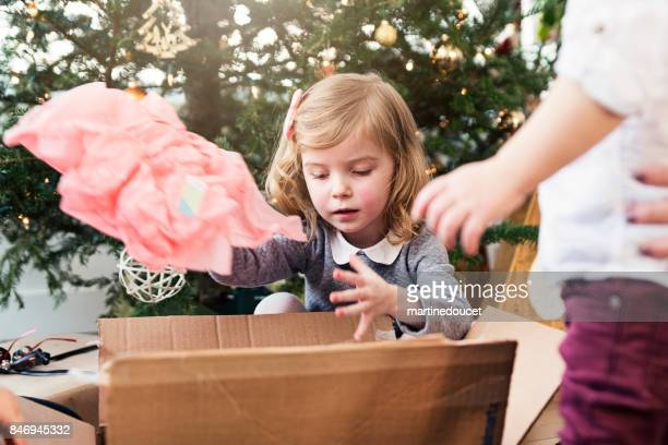 Opening gifts on Christmas morning for small family.