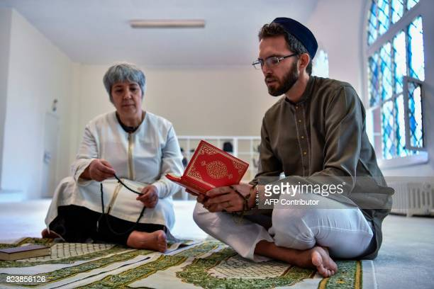 Openly gay French imam LudovicMohamed Zahed reads verses of the Koran as GermanTurkish lawyer author and activist Seyran Ates listens prior to Friday...