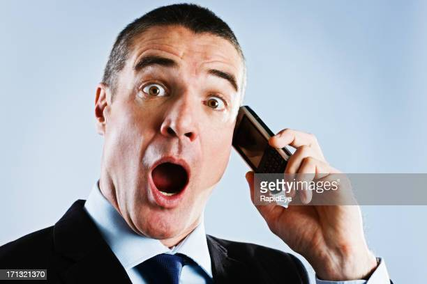 Open-mouthed mature businessman shocked by something heard on the phone