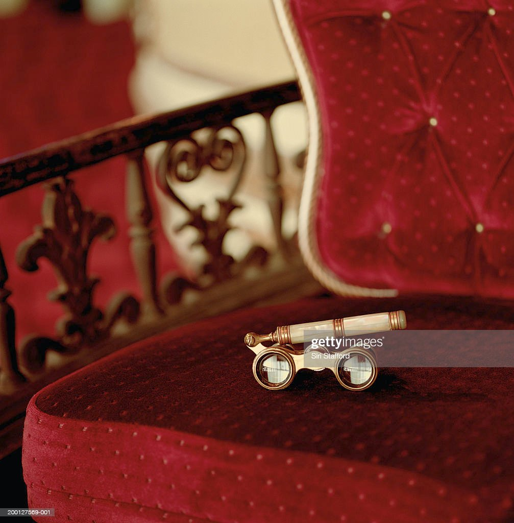 Opera glasses sitting on red chair in theater, close-up : Stock Photo