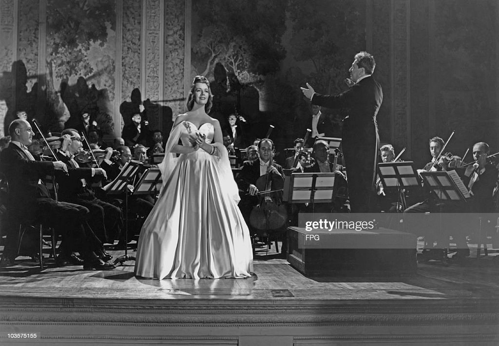 Opera singer Lily Pons alongside conductor Charles Previn in a scene from the film 'Carnegie Hall' USA 1947 Previn is pictured conducting the...