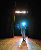 Opera singer performing on stage, reaching toward spotlight, rear view