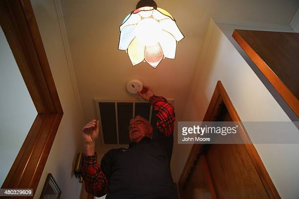 'Operation FixIt' technician Manfred Shultz changes the batteries on a smoke detector inside a senior's home on March 24 2014 in Ledgewood New Jersey...