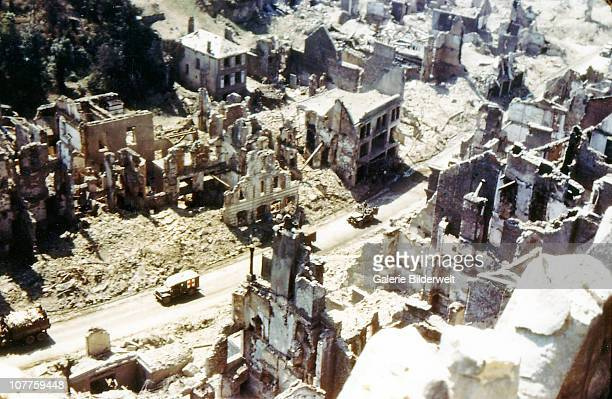 Operation Overlord Normandy An American ambulance a jeep and other vehicles are driving through the ruins of SaintLo August 1944 The town was almost...