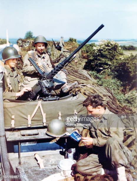 Operation Overlord Normandy United States Army soldiers are sitting on top of several M4 halftrack armored personal carriers One is reading a book...