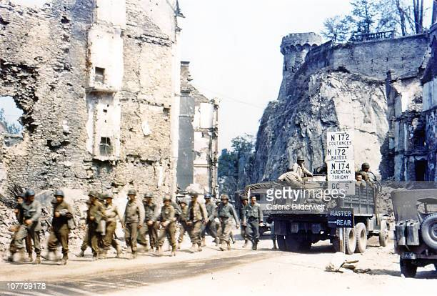 Operation Overlord Normandy United States Army trucks and jeeps are driving through the ruins of SaintLo July 1944 A group of American soldiers is...