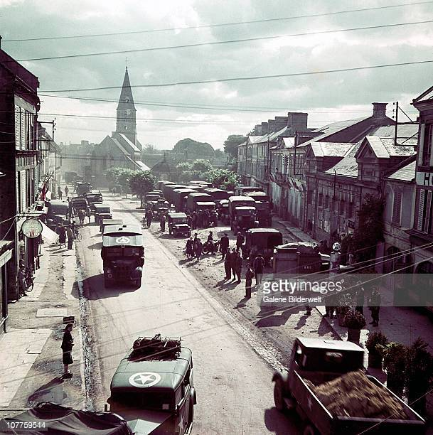 Operation Overlord Normandy United States Army trucks jeeps and other vehicles have entered a town in Normandy France June 1944 They are part of the...